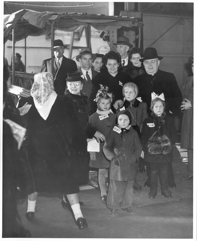 Bishop Mulloy posing with a DP family at Ellis Island