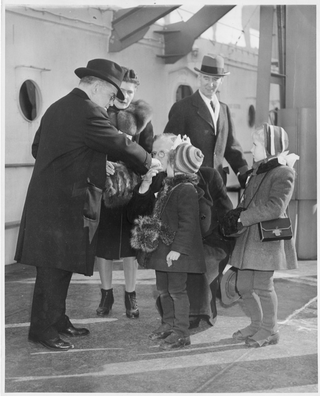 Displaced Persons interact with Bishop Mulloy at Ellis Island